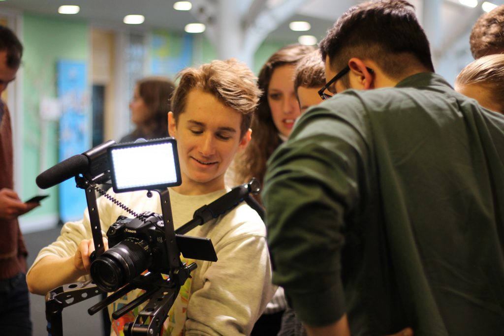 Me filming with a camera rig and discussing a shot with a group