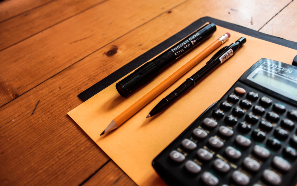 A picture of a pen and pad on a wooden table