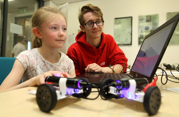 Me sitting with a young girl at a laptop with a wheeled Arduino robot